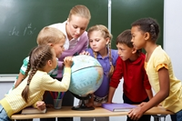 The picture depicts a teacher and five children in a classroom standing and looking at a globe.