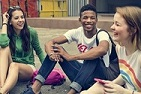 PISA Foreign Language - teenage students sitting on the ground laughing